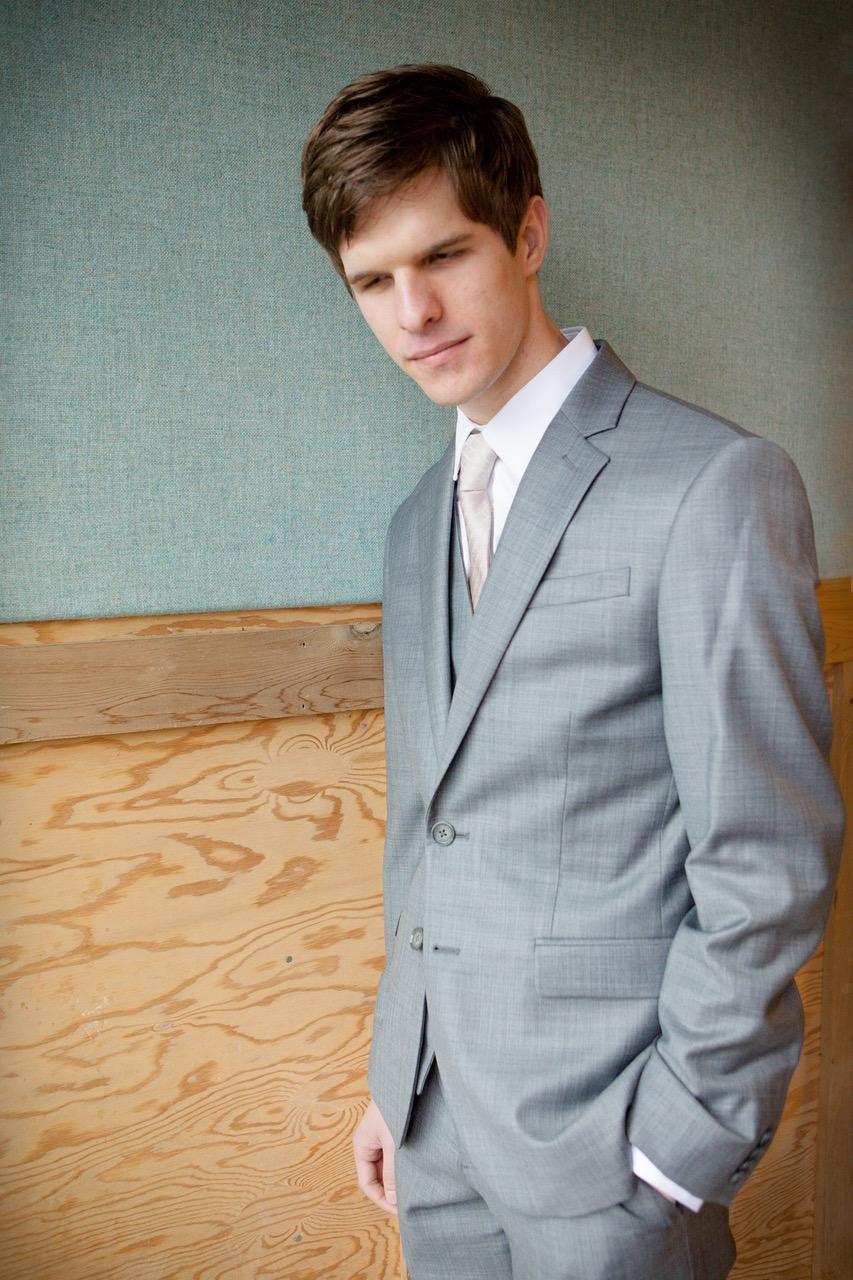 Mac Potts wears a grey suit with a beige tie.