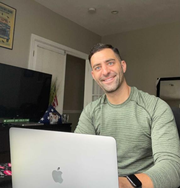 Dustin Feldman, a white man with dark hair, sits with his laptop